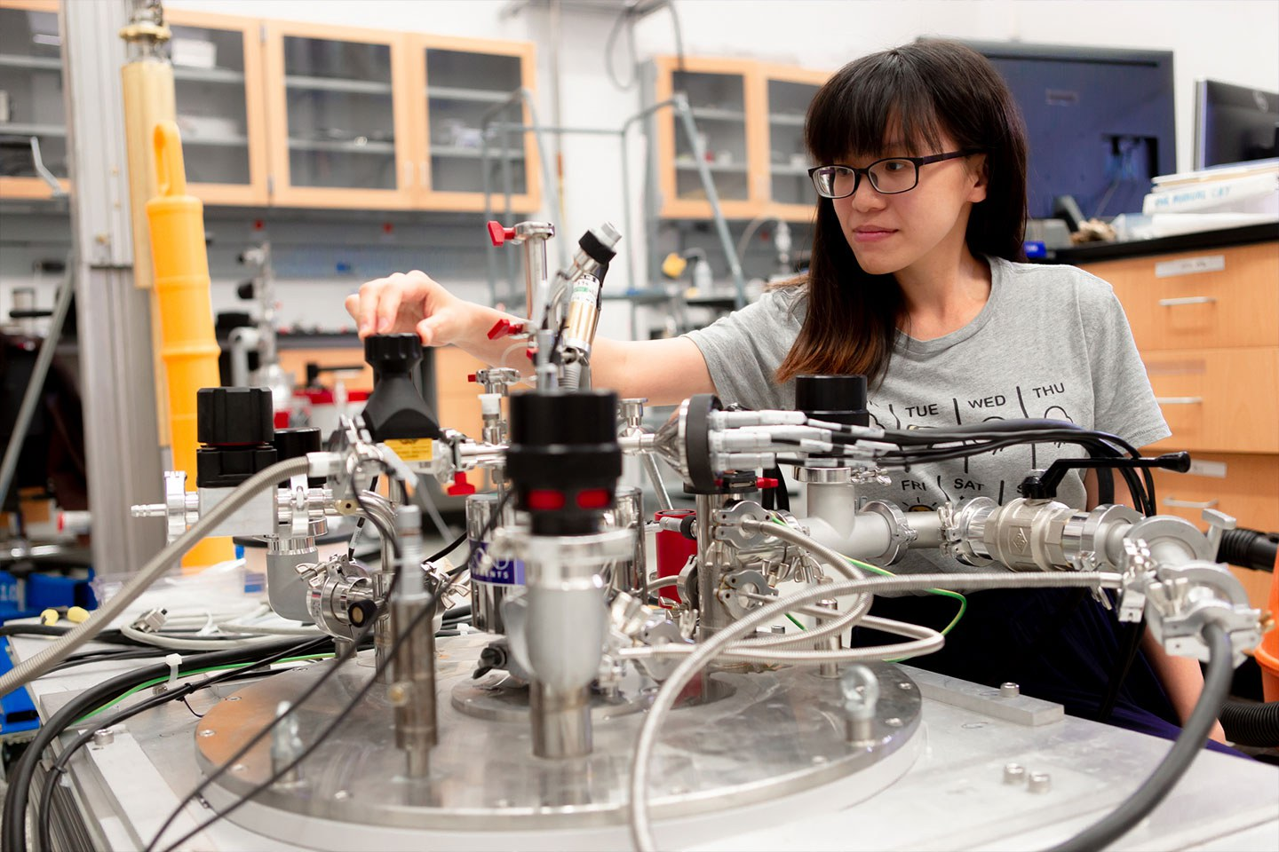Individual standing behind and making adjustments to laboratory equipment